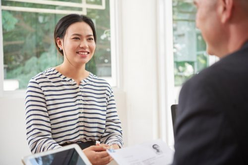 Asian young woman introducing her resume to the interviewer in a job interview at office